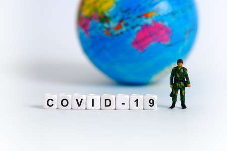 Global lockdown conceptual photography because of coronavirus – miniature soldier stands in front of earth globe and word beads. Image Photo
