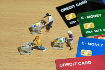 Contact-less payment. Group of people shopping using electronic money (e-money). Miniature people figurines toys conceptual photography.