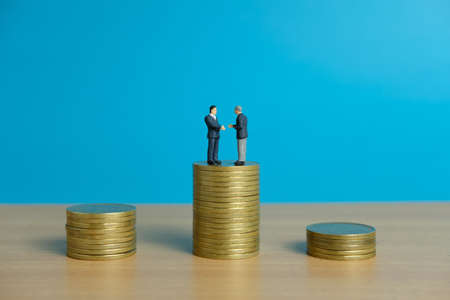Miniature business concept - two businessman make an handshake for partnership agreement handshake with coin stack