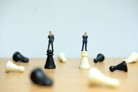 Business strategy conceptual photo - two miniature businessmen standing on castle chess piece