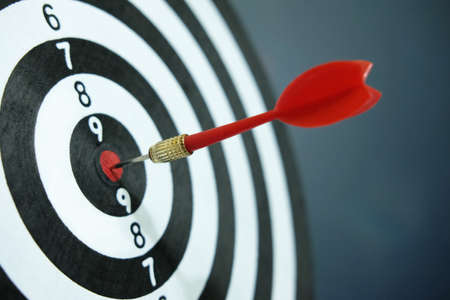 Conceptual photo of business strategy / accuracy - a red arrow that sticks directly in the center of the target dartboard