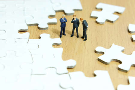Business strategy conceptual photo - Group of miniature businessman have a discuss above puzzle jigsaw