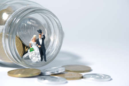 Wedding budget concept miniature people, toys photography. Bride and groom with coin money on a jar glass isolated on white background. Image photo