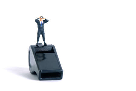 Businessmen using binoculars standing above black whistle. Miniature tiny people toys photography. isolated on white background.