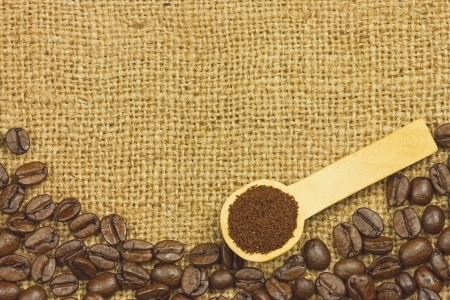 croud: Coffee ground in spoon on coffee seeds and sack Stock Photo