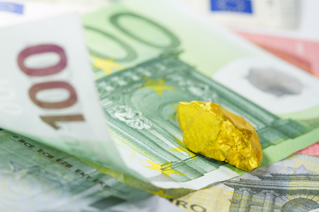 Gold nugget on euro banknotes Stock Photo