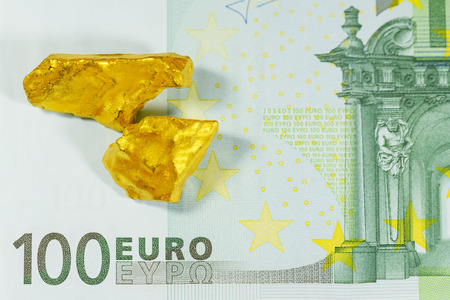 an ounce: Golden nuggets on euro banknotes close up