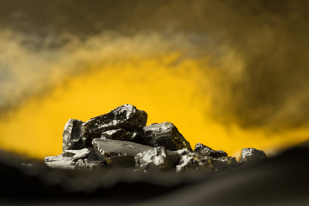 Raw coal nuggets on golden textured background Stock Photo
