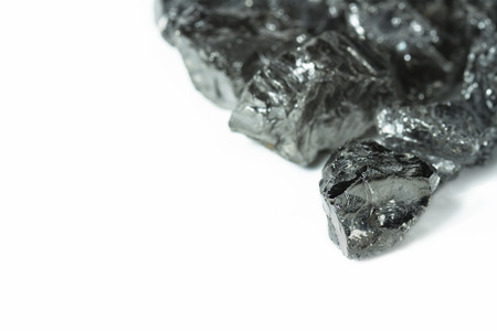 Raw coal nuggets on white background with blured foreground. Nuggets of raw coal isolated on white background