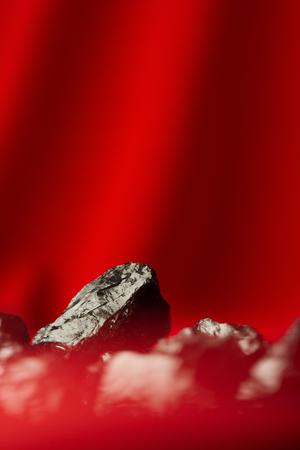 Black raw coal nugget on red soft backgroundsoft Reklamní fotografie