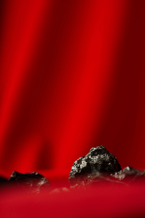 Raw coal nuggets on red soft  background Stock Photo