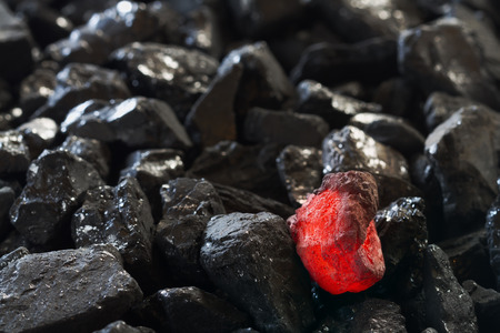 Red hot coal nugget on focus on other cold raw nuggets of coal. Background of raw coals with soft focus exclusion with color and temperature.