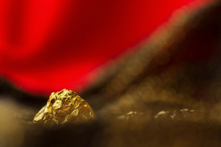 Golden nugget on red soft  background with glitter lights Stock Photo