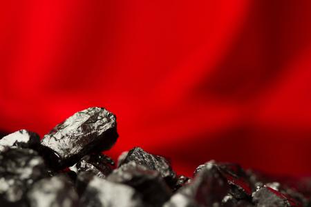 Nuggets de charbon brut sur fond rouge doux