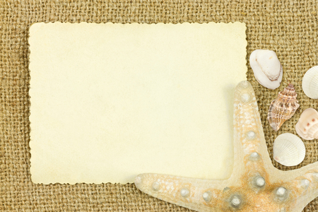 reverse: Reverse side of an old photo print with a decorative border sea star and sea sheels on sack cloth  background Stock Photo