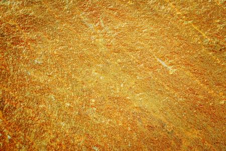 Wet golden surface texture close up. Golden nugget wet surface