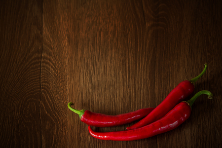 Red peppers on the brown table. Hot peppers on wooden background. Chilli peppers background with copy space Reklamní fotografie