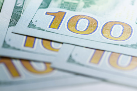 Stack of one hundred dollar banknotes close up with selective focus