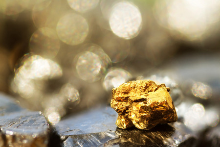 Golden bar on raw coal nuggets with soft focus and shiny background Stock Photo
