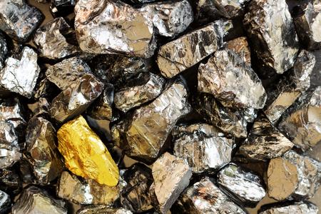Golden bar on background of raw coal nuggets close-up Reklamní fotografie
