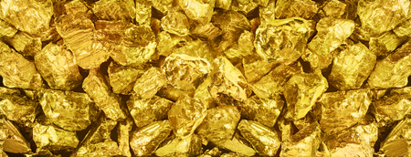 |Big panorama photo of many golden nuggets close-up. Wide background of shiny golden bars. Golden ingot  close-up on wide background.