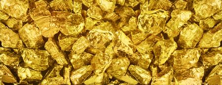 |Großes Panoramafoto von vielen goldenen Nuggets Nahaufnahme. Breiter Hintergrund von glänzenden goldenen Balken. Goldene Barrennahaufnahme auf breitem Hintergrund. Standard-Bild