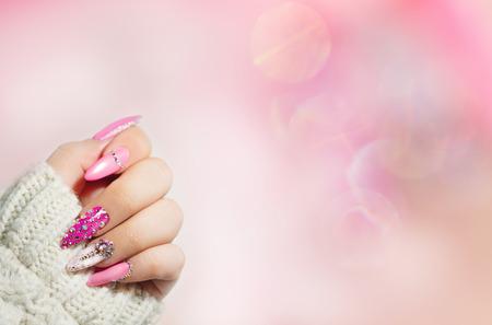 Bunte Nagelkunst. Maniküre. Helle Maniküre im Urlaubsstil mit Edelsteinen und Funkeln. Nagelpolitur. Mode mit Diamantglanz, trendige Accessoires. Schönheit hände. Stilvolle Nägel, Nagellack.