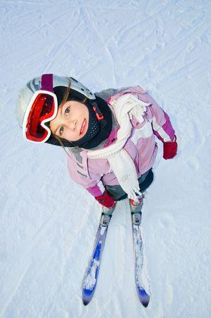looking upwards: girl in ski gear looking upwards at a ski resort in Finland