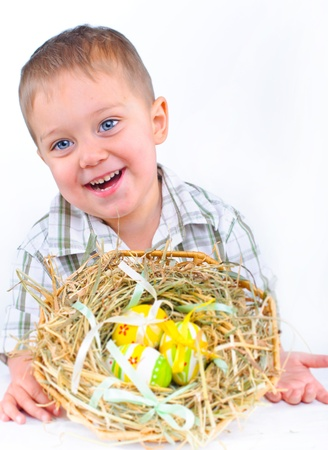 Little boy with easter eggs in basket photo