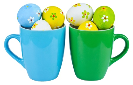 Easter eggs in cups on white background photo