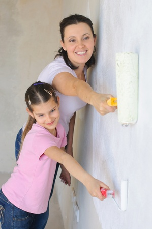 Mother and douther painting a wall with roller Stock Photo - 9275099