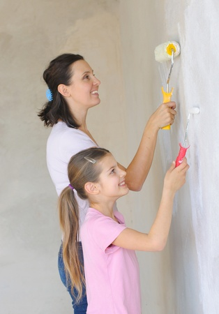 Mother and douther painting a wall with roller Stock Photo - 9275094