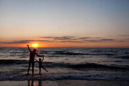 douther: Silhouettes of father and his douther on beach at sunset Stock Photo