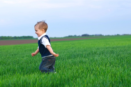 A beautiful little boy runing in the grass photo