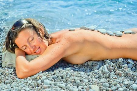 stone bowl: Attractive happy woman getting spa treatment
