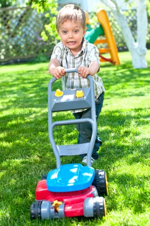 lawn mower: Young helper Stock Photo