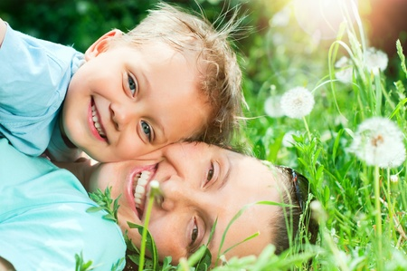 Cute boy with mother lying in the grass  photo