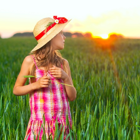 Cute girl on wheat. Stock Photo - 9646894
