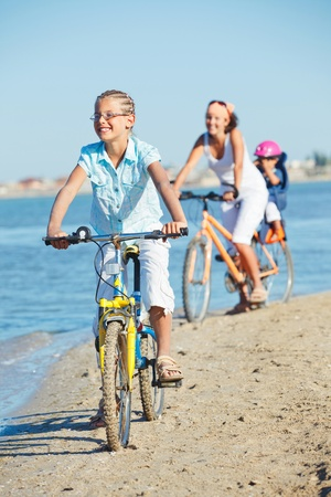 Cute girl with her mother and brother ride bikes photo