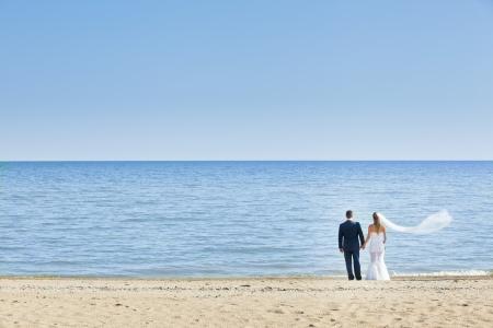 gelukkige bruidspaar staan op het strand Stockfoto