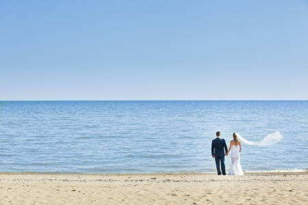 woman beach dress: happy wedding couple standing on beach