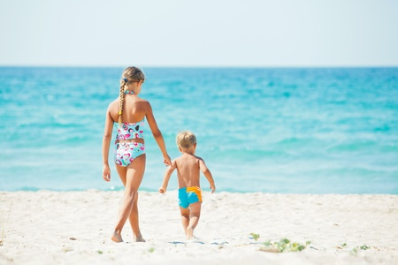 Young girl and boy playing happily at pretty beach photo