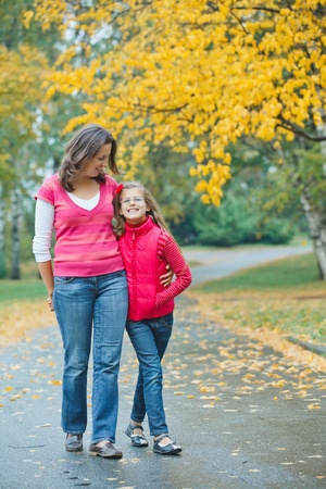 raincoat:  Cute girl with her mother walking in park Stock Photo