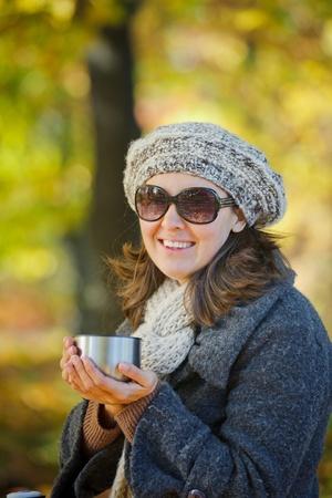 Woman drinks tea in autumn park photo