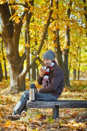 Man drinks tea in autumn park photo