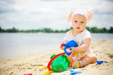 baby sitting: Little cute girl on the beach