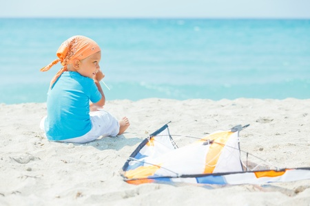 Cute boy on beach playing with a colorful kite Stock Photo - 11770027