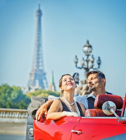 Pareja feliz sonriente en un coche. Romance en París. Foto de archivo