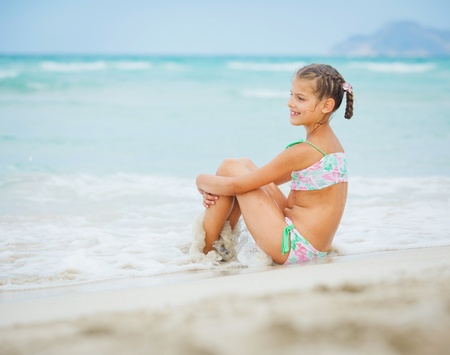 Adorable happy little girl on beach vacation photo