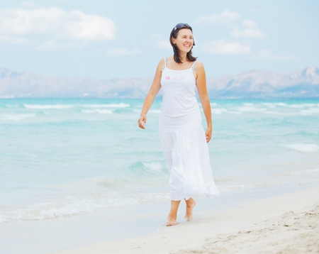 successfull: young woman walking near blue sea.